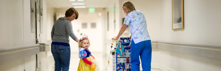 little girl playing dress-up with mom and MUSC staff